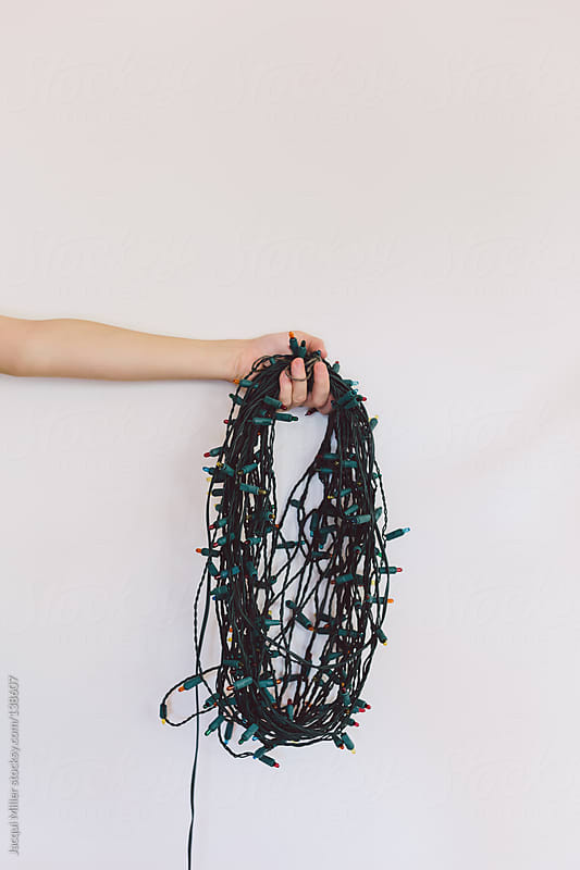 Girl holds a long string of Christmas lights in her hand.  by Jacqui Miller for Stocksy United