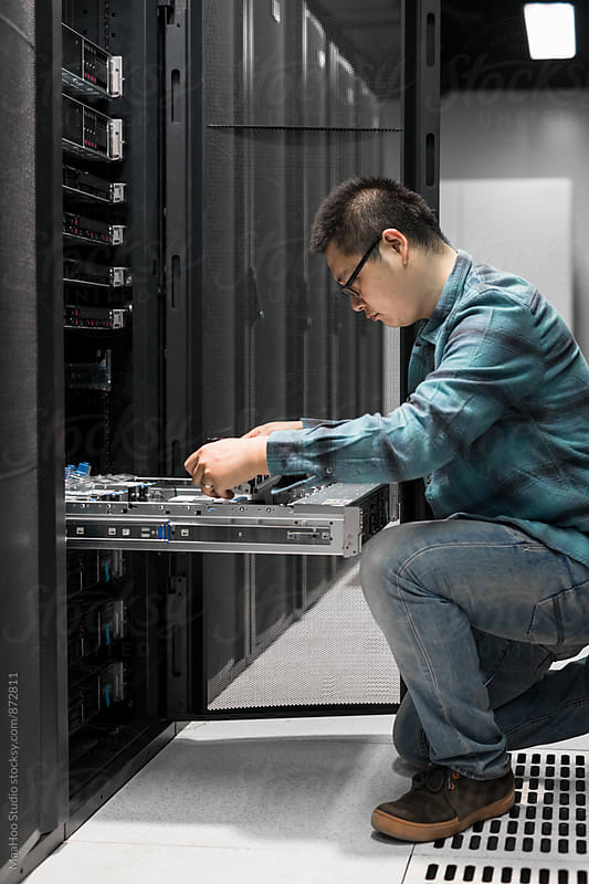 Young engineer working in datacenter by Maa Hoo for Stocksy United