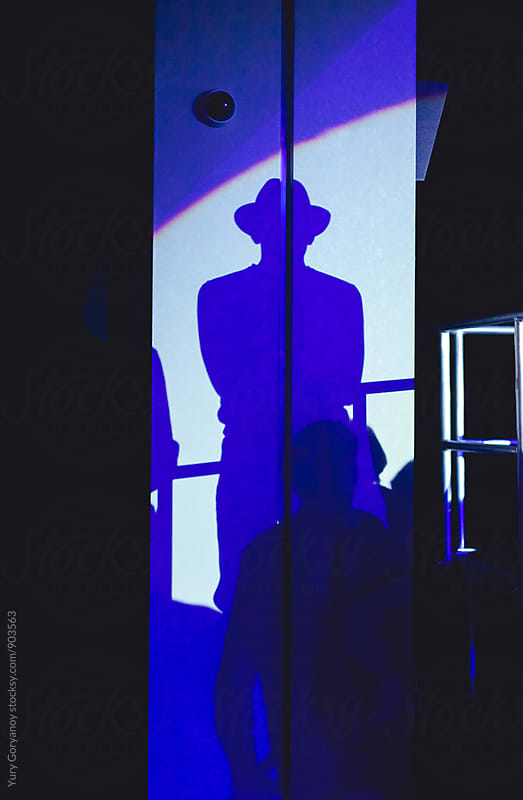 Shadow man in a hat on a wall by Yury Goryanoy for Stocksy United