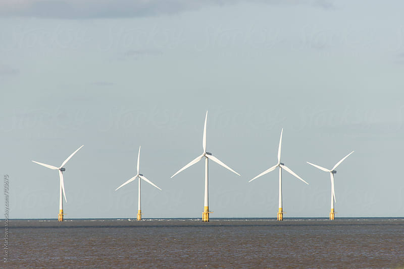 Five wind turbines in a row at sea by Mike Marlowe for Stocksy United