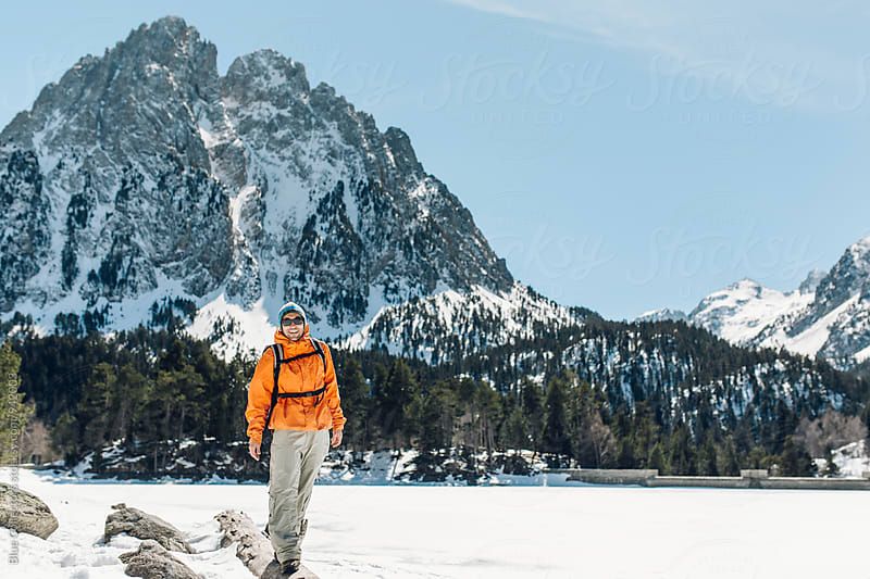 Male mountaineer smilingly over the rocks watching the snowy landscape. by Jordi Rulló for Stocksy United