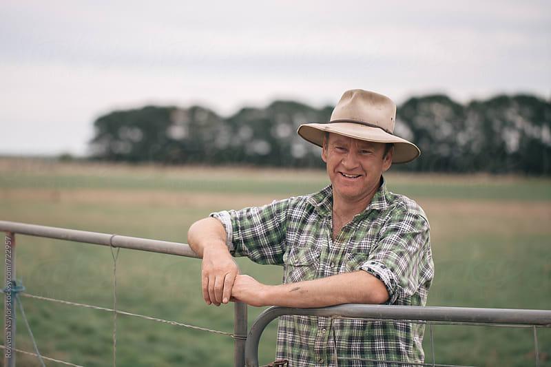 Farmer behind farm gate by Rowena Naylor for Stocksy United