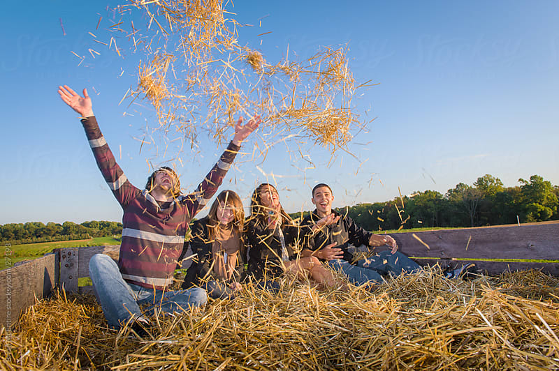 Young adults having fun out doors during an Autumn hay ride.  by Brian McEntire for Stocksy United