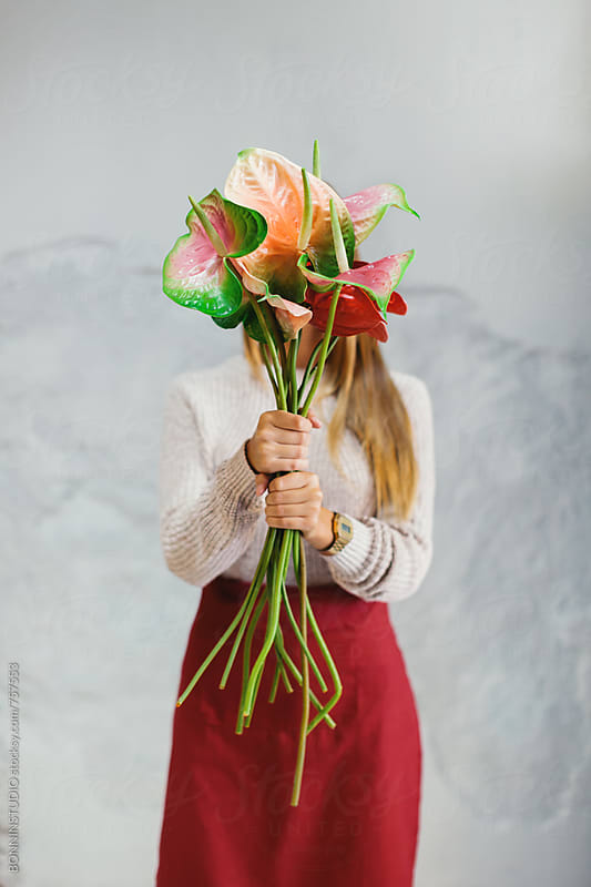 Woman covering her face with a bouquet of flowers. by BONNINSTUDIO for Stocksy United