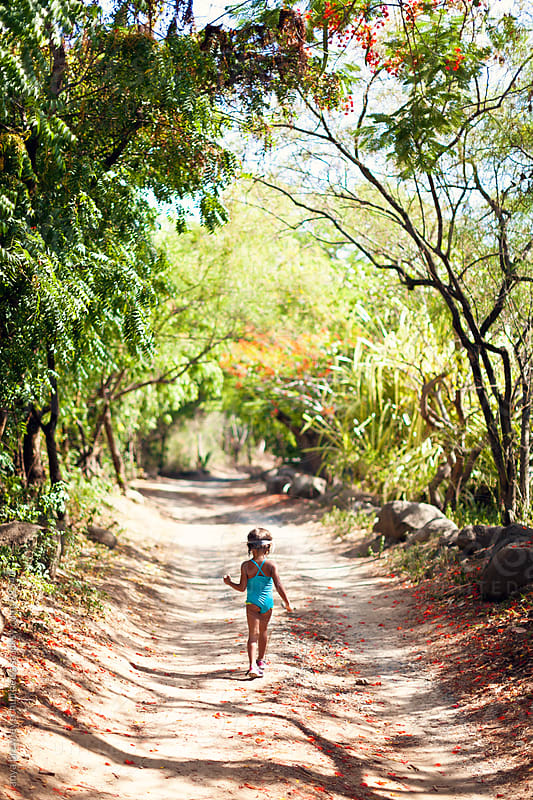 Girl in blue bathingsuit walking along sunny path by anya brewley schultheiss for Stocksy United