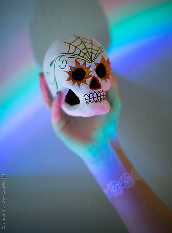 Painted sugar skull being help up against a prism by Carolyn Lagattuta for Stocksy United