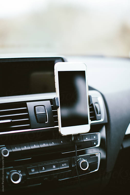 mobile phone on the panel in the car by Javier Pardina for Stocksy United