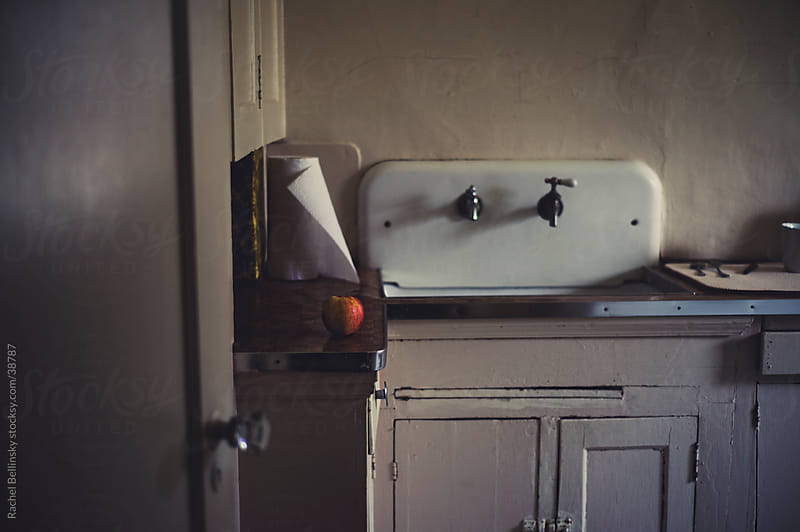 Vintage sink and kitchen with apple in soft light by Rachel Bellinsky for Stocksy United