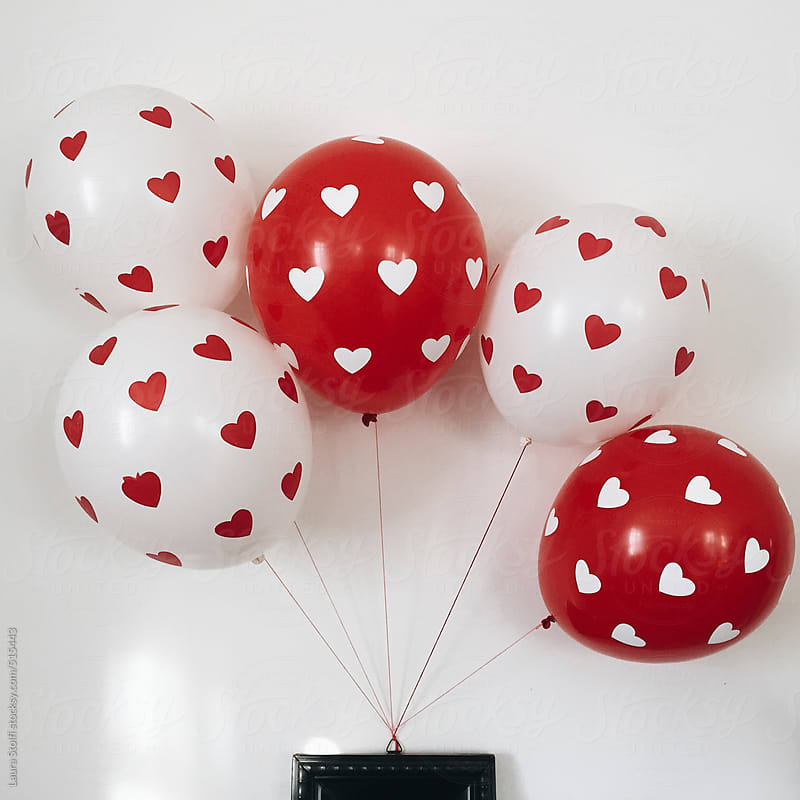 White and red balloons with hearts on them hanging from wooden frame.  by Laura Stolfi for Stocksy United