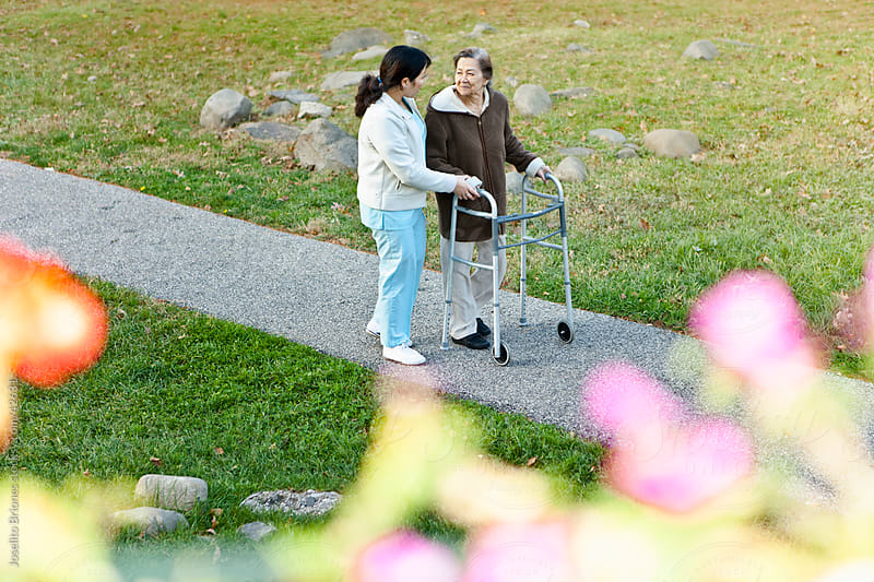 Home Caregiver Helps Senior Citizen Patient Exercise by Joselito Briones for Stocksy United