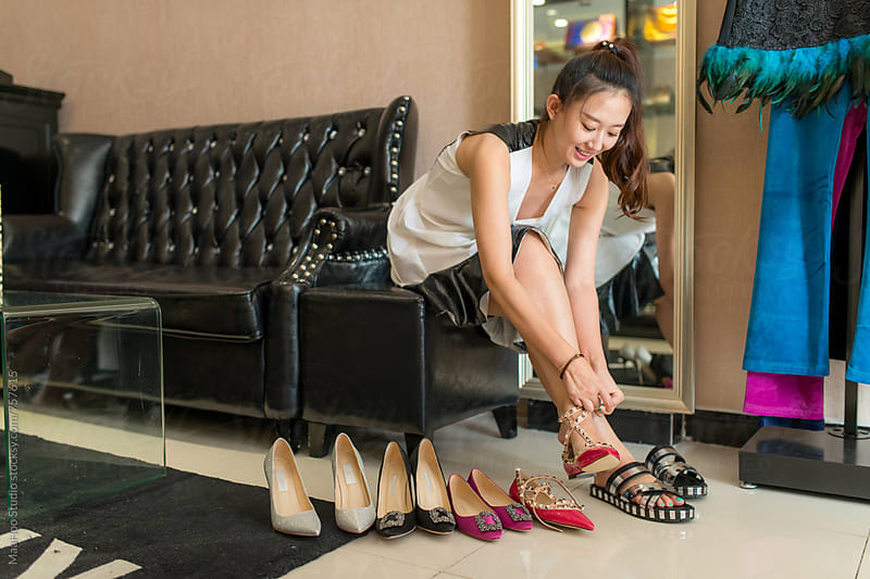 Young woman trying shoes in store by Maa Hoo for Stocksy United