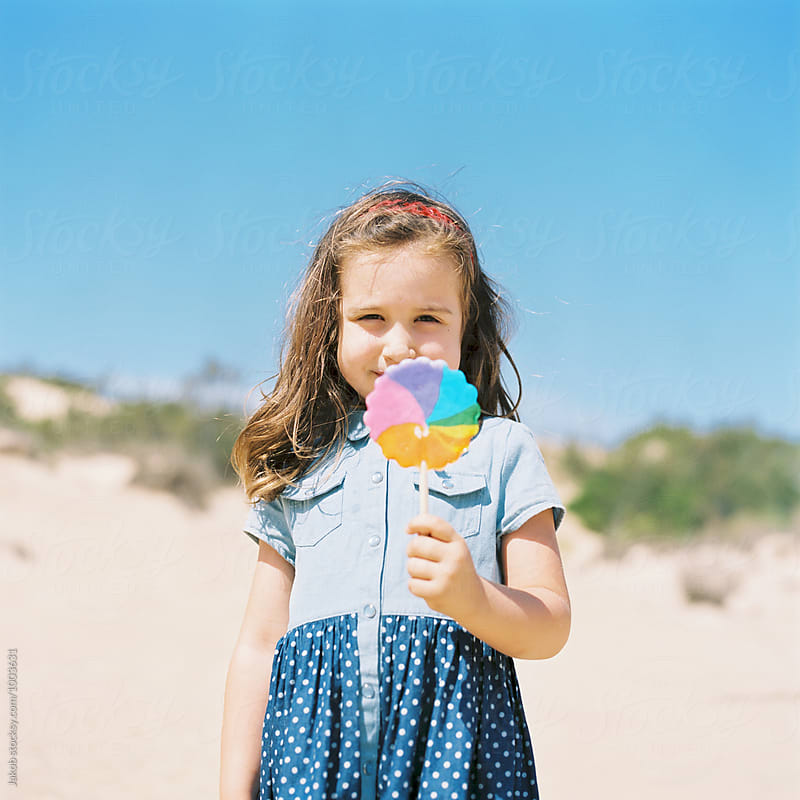 Beautiful young girl in a dress standing on a sand dune holding a lollipop by Jakob for Stocksy United