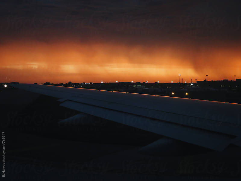 On a Plane Overlooking Storm Clouds as the Sun Sets by B. Harvey for Stocksy United