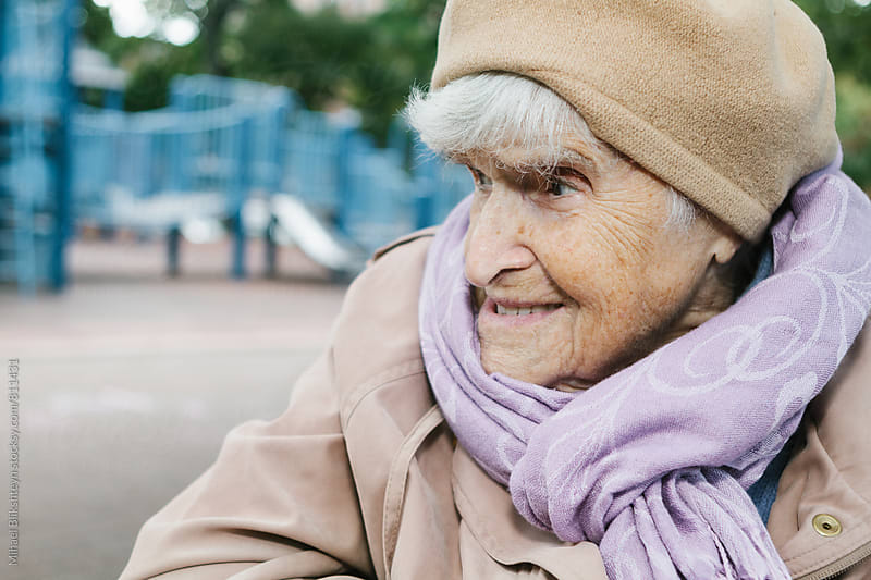 Portrait of a sweet elderly woman in her 90s outside at a playground in the park by Mihael Blikshteyn for Stocksy United