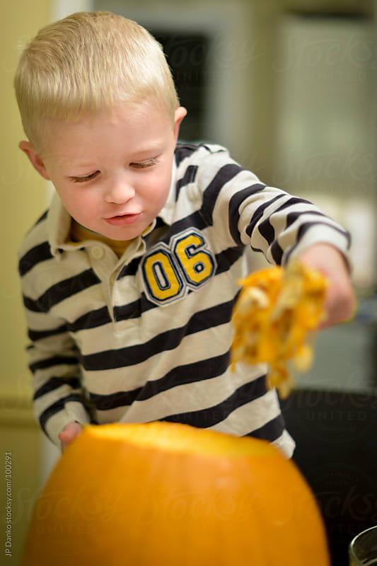 Little Boy Carving Halloween Pumpkin with Pumpkin Seeds by JP Danko for Stocksy United