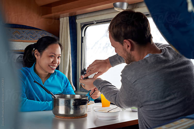 Couple eating in campervan  by Daxiao Productions for Stocksy United