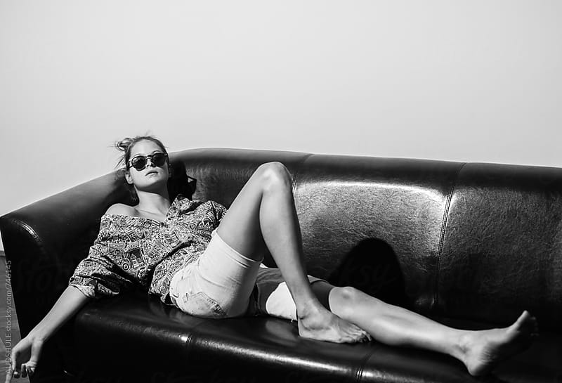 Feshinable trendy female in hip outfit  lying on black sofa  by Audrey Shtecinjo for Stocksy United