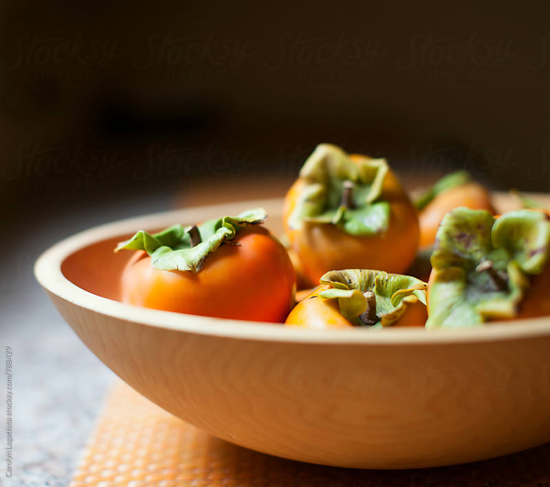Wooden bowl filled with organic persimmons by Carolyn Lagattuta for Stocksy United