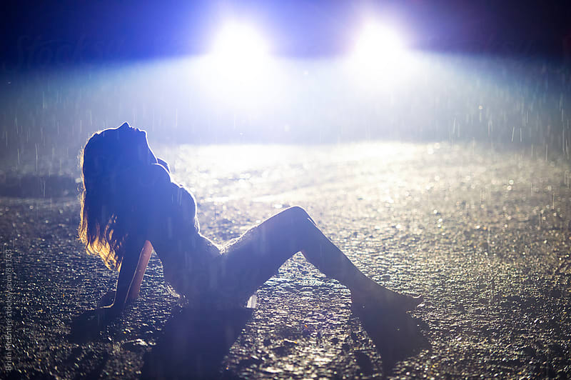 Woman leaning back in rain. Night, illuminated by car head lights. by Brian McEntire for Stocksy United