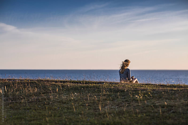 Woman sitting by the sea at sunset by Lior + Lone for Stocksy United