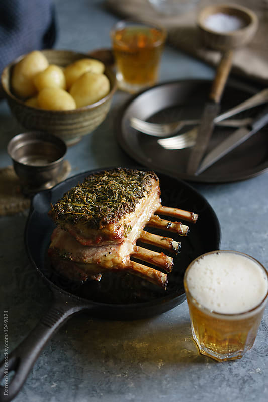 Herb crust rack of lamb in cast iron skillet. by Darren Muir for Stocksy United