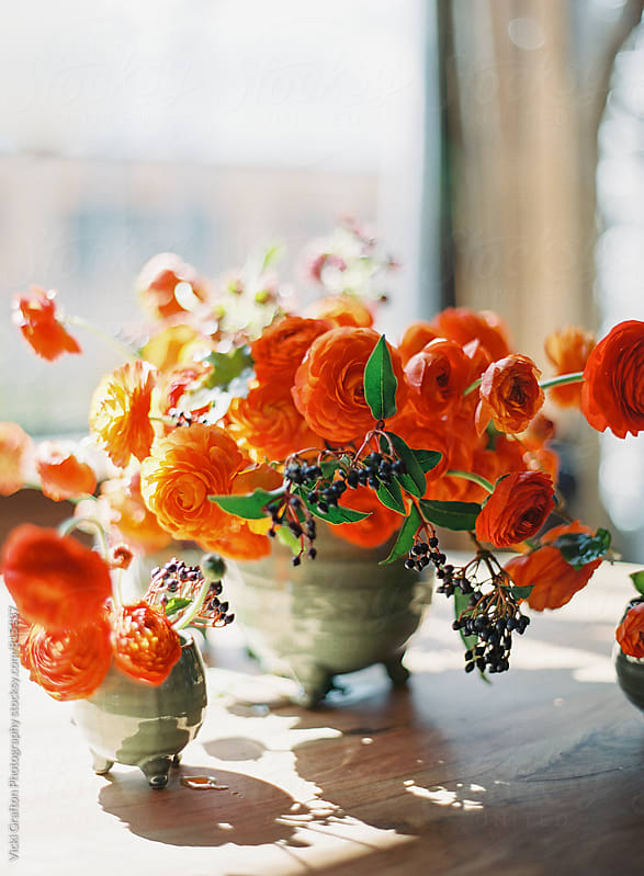 Orange floral arrangement on table  by Vicki Grafton Photography for Stocksy United