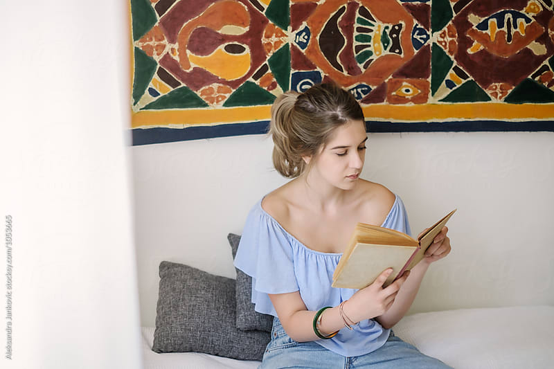 Woman Sitting on the Bed Reading a Book by Aleksandra Jankovic for Stocksy United