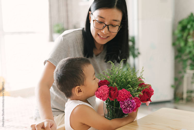 Cute toddler boy holding flowers with his mother by Maa Hoo for Stocksy United