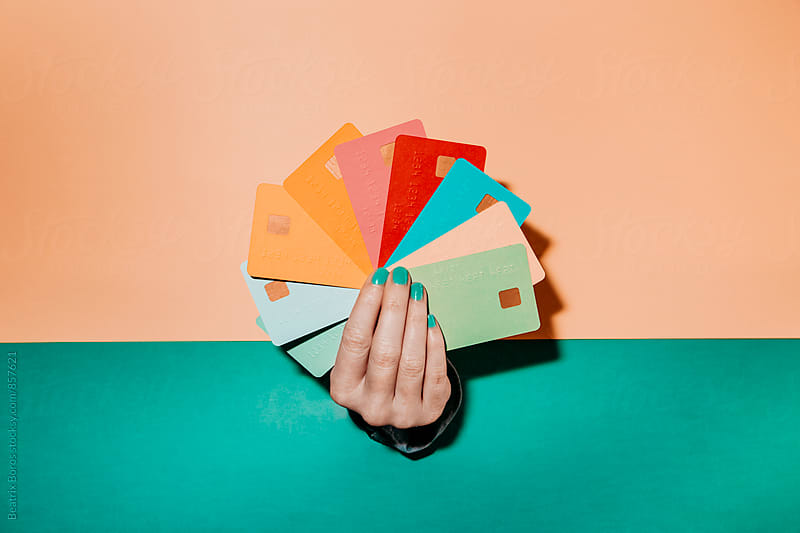 Hand coming through a wall holding several credit cards by Beatrix Boros for Stocksy United