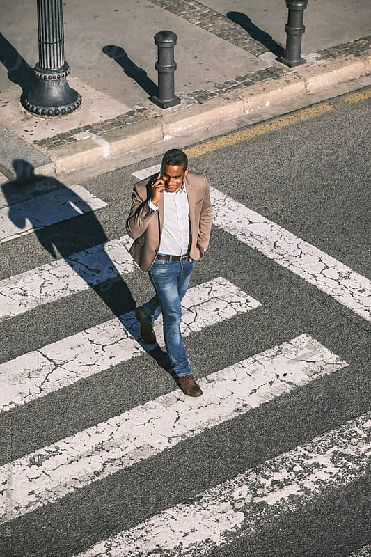 Black businessman walking and talking with cell phone on a city crosswalk. by BONNINSTUDIO for Stocksy United