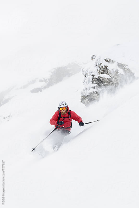 Skier taking a sharp turn splashing with snow by RG&B Images for Stocksy United