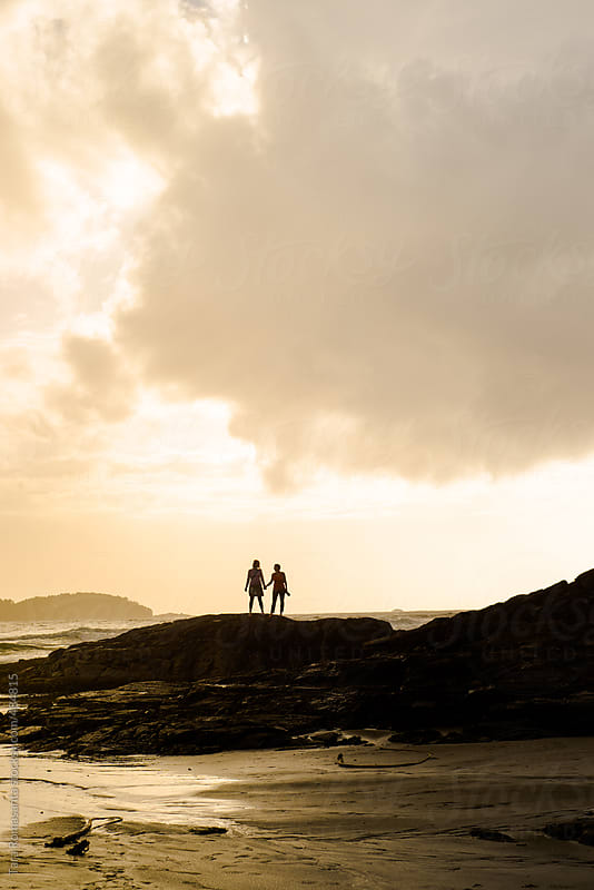 friends holding hands, standing on rocks at the sea shore by Tara Romasanta for Stocksy United