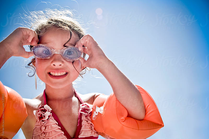 young girl holding swimming goggles  by Tomas Kraus for Stocksy United