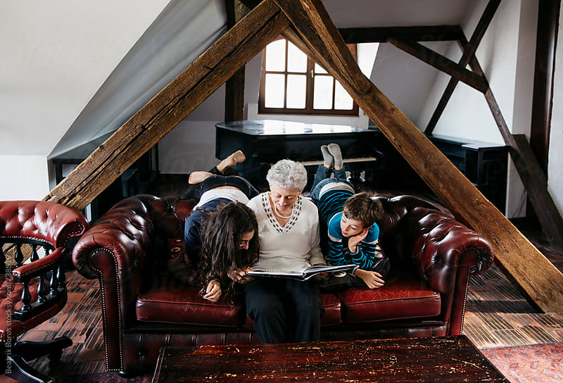 Grandma and grandchildren reading a book together by Beatrix Boros for Stocksy United