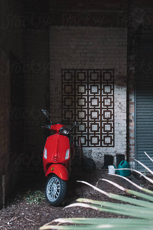 Red scooter parked in garage by Rowena Naylor for Stocksy United