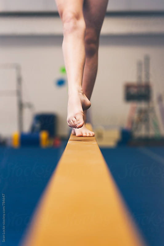 Gymnastics: Girl Pointing Toes On Balance Beam by Sean Locke for Stocksy United