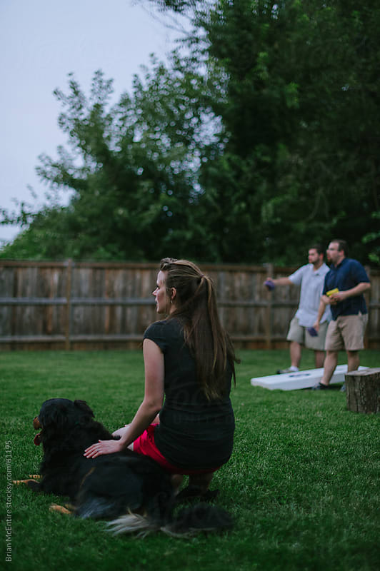 Woman Guest Petting Family Dog Watching Game At Backyard Party by Brian McEntire for Stocksy United