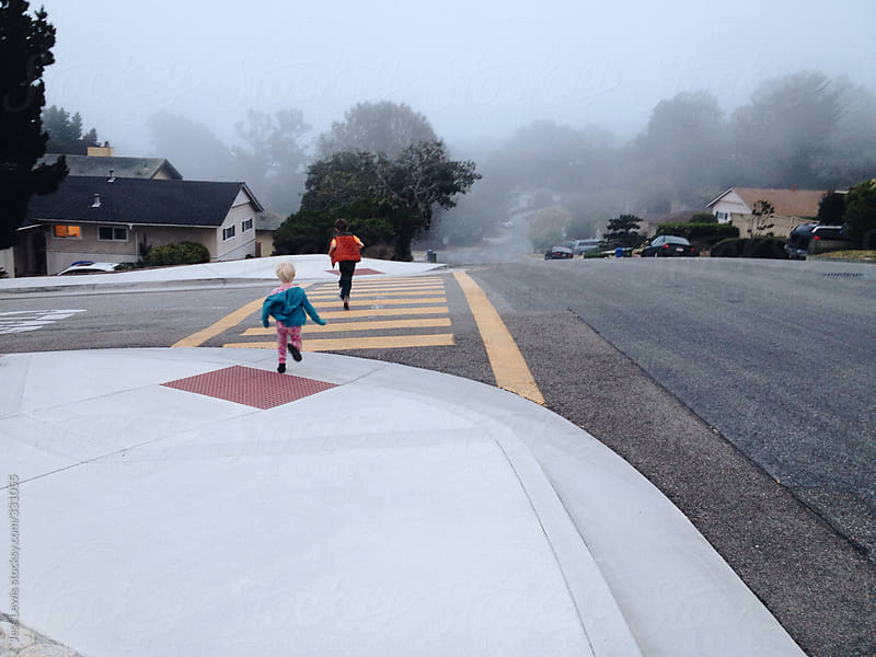 two children running across street on foggy day by Jess Lewis for Stocksy United