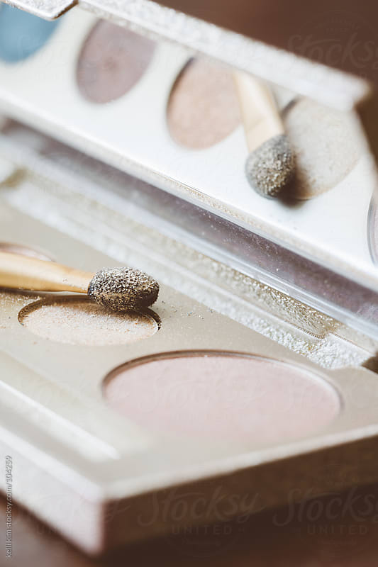 Macro Of Pretty Glittered Eyeshadows And Applicator With Reflection by kelli kim for Stocksy United