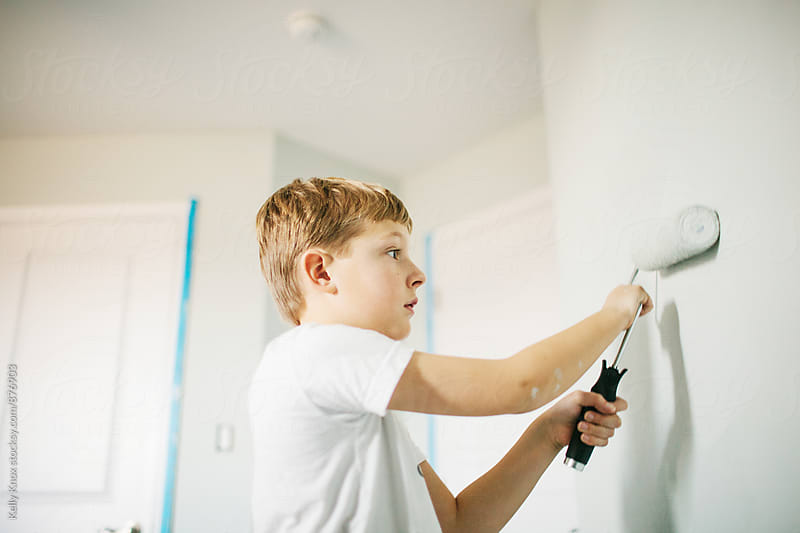 boy using a paint roller to paint a room  by Kelly Knox for Stocksy United