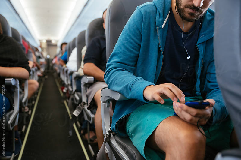 Young man using his phone with headphones in an airplane during a flight by Alejandro Moreno de Carlos for Stocksy United