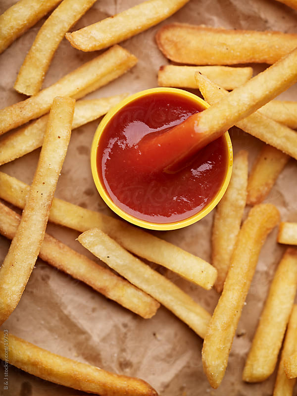 french fries and ketchup by B & J for Stocksy United