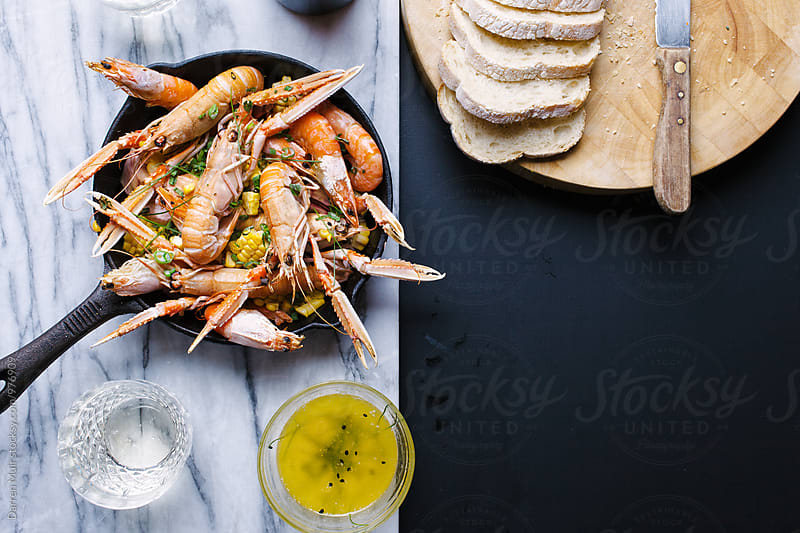 Roasted langoustines and shrimps on a bed of smoked garlic with corn. by Darren Muir for Stocksy United