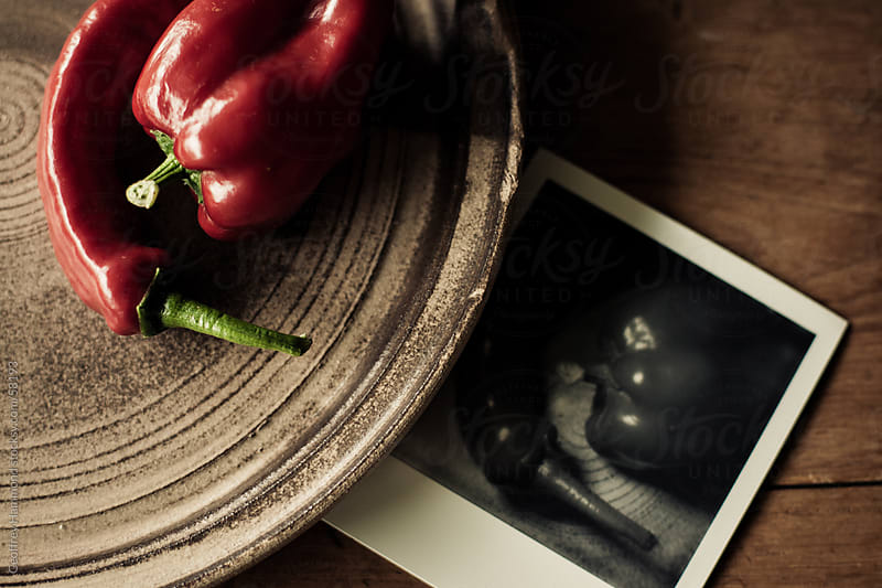 Two Red Peppers on Rustic Plate and Instant Photo by Geoffrey Hammond for Stocksy United