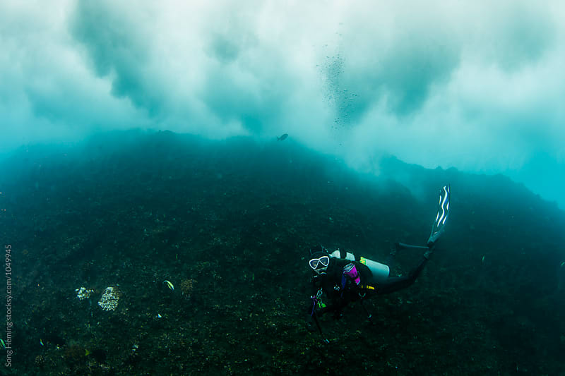 A scuba diver diving under big wave by Song Heming for Stocksy United