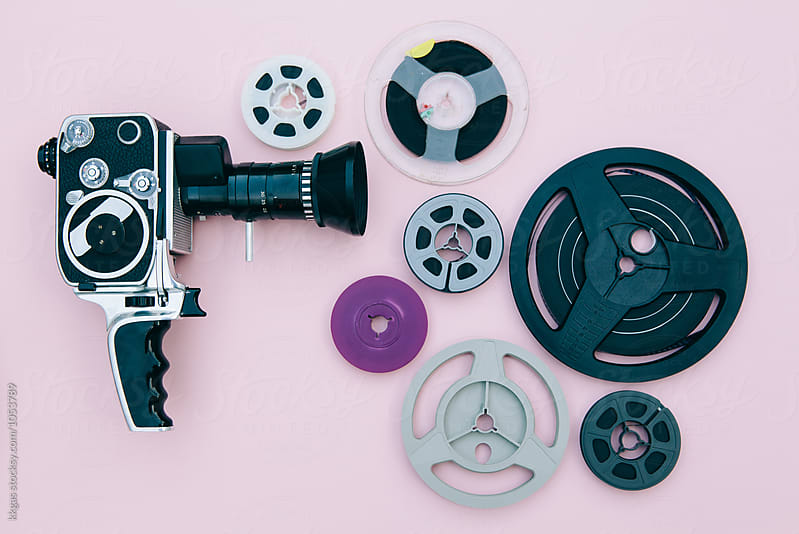 Vintage cinema camera and reels over pink background by kkgas for Stocksy United