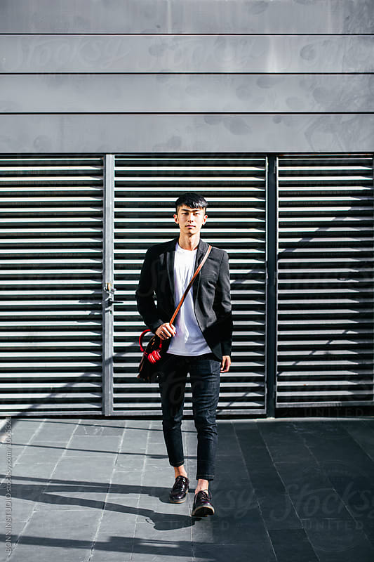 Young asian businessman walking on the street.  by BONNINSTUDIO for Stocksy United