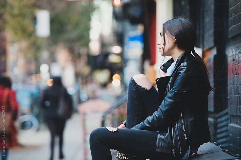 Young woman sitting alone outside in the city by Lauren Naefe for Stocksy United