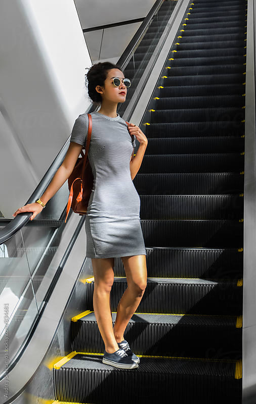 Young stylish woman on escalator stairs. by Marko Milanovic for Stocksy United