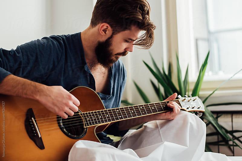 Bearded Man Playing Guitar in Bed by Nemanja Glumac for Stocksy United